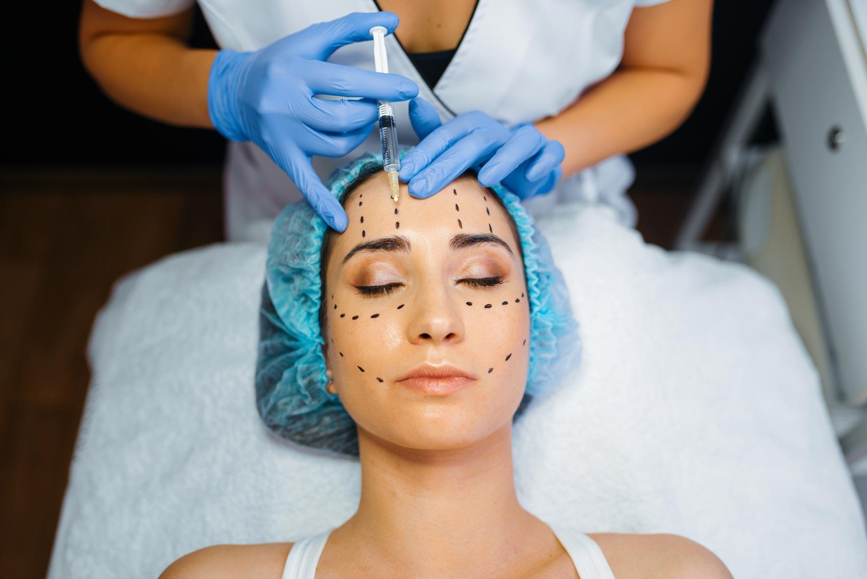 Mujer recibiendo de cosmetóloga tratamiento de ácido hialurónico en la frente