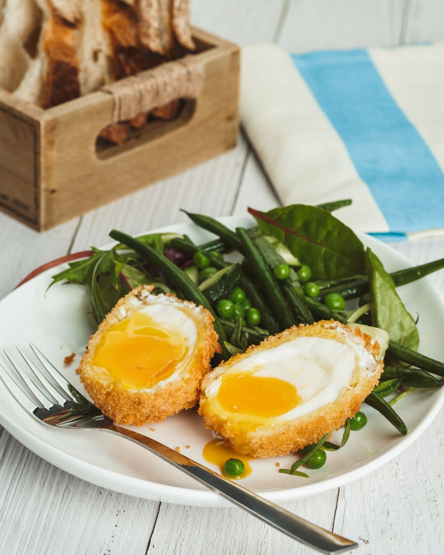 Crispy eggs with a summer salad on plate and bread in the background