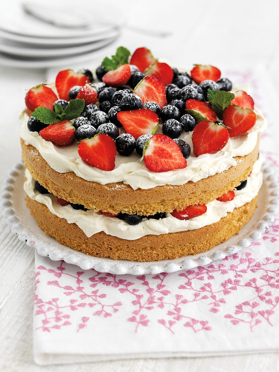 Beautiful Berry Sponge Cake with Vanilla Cheesecake Filling on plate with serving cloth