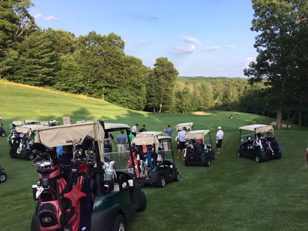 A Par 3 shootout golf tournament with many golf carts and golfers