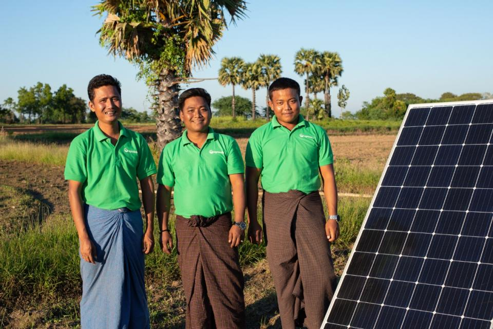 A group of third-world entrepreneurs standing next to a solar panel.