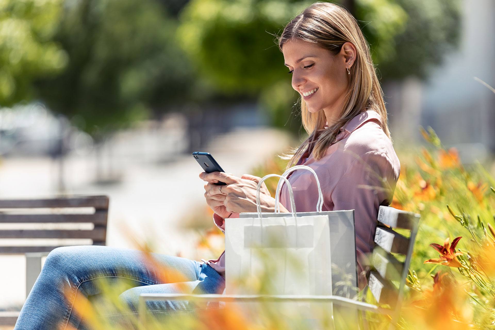 Beautiful woman sitting on a park bench with a shopping bag, using her mobile phone.