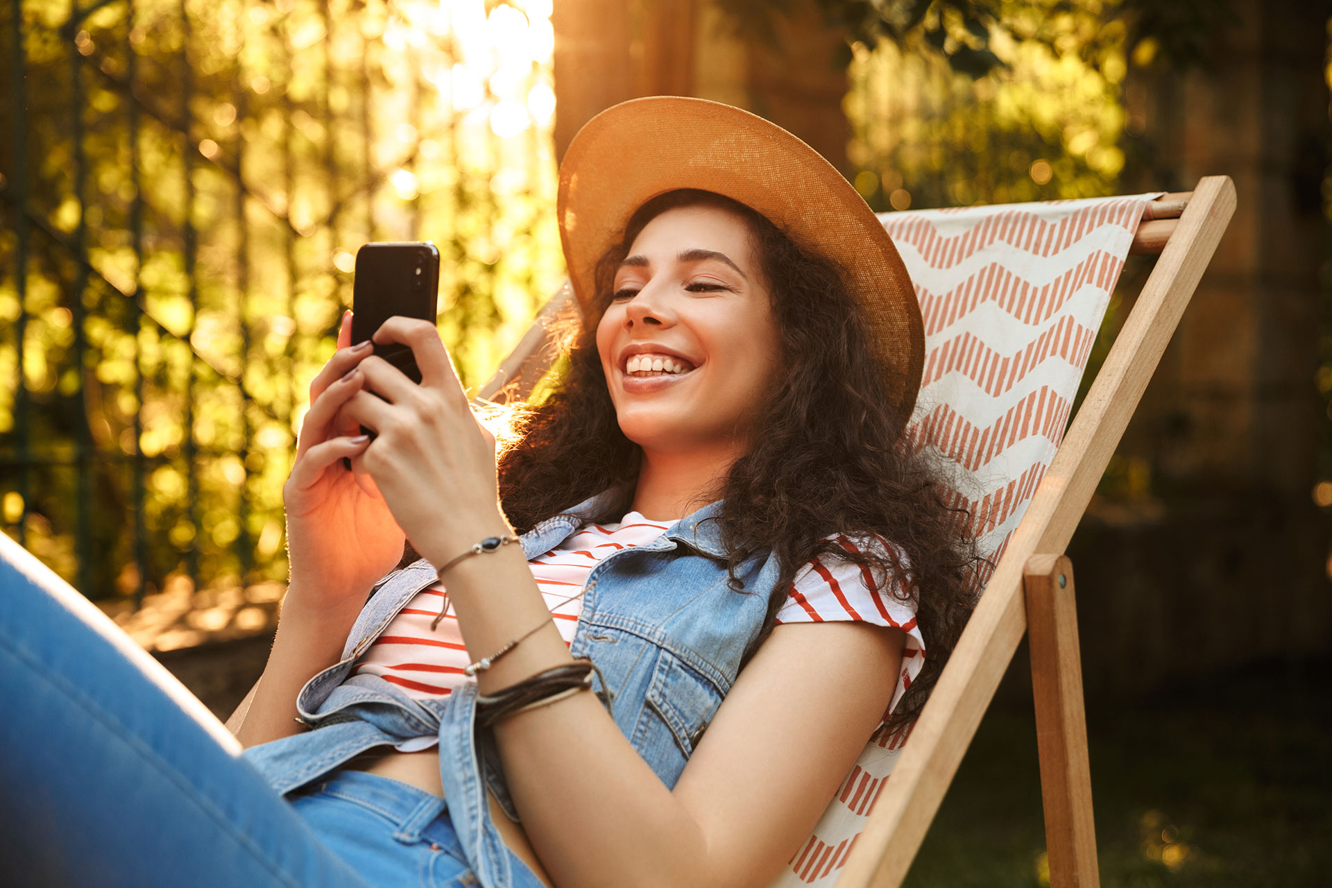 Happy young woman relaxing in a lawn chair, smiling at her mobile phone.