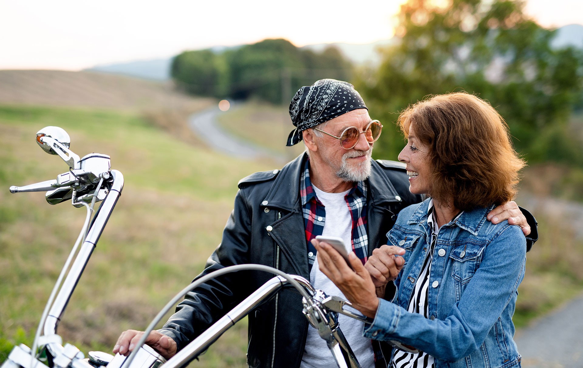 Happy senior couple using their mobile phone on a motorcycle road trip.