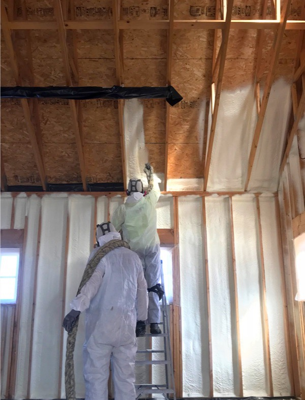 two spray foam applicators installing installation in new home