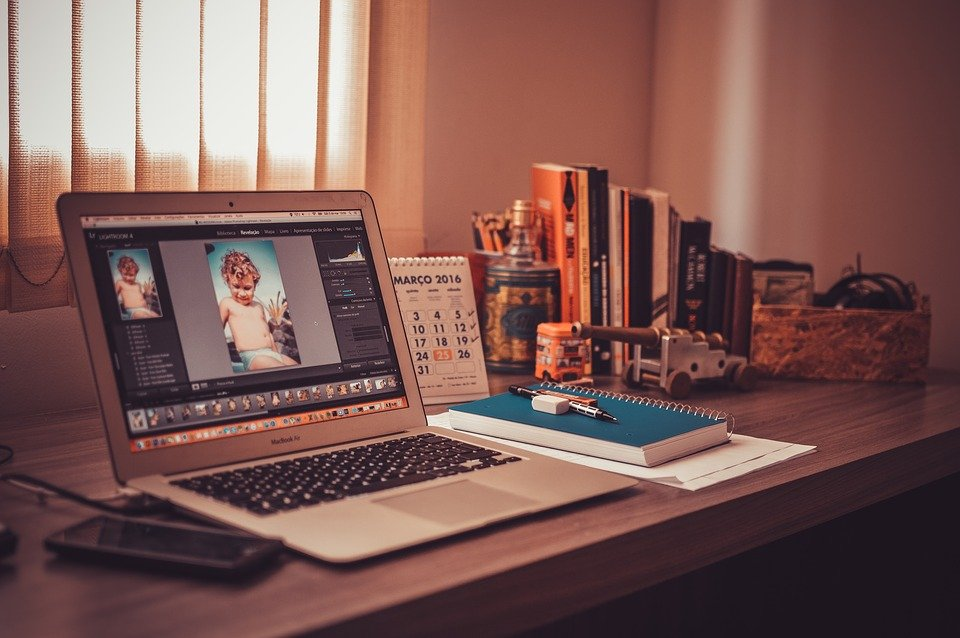 Working from home can prove to be beneficial or detrimental depending on the employee. The picture shows a Macbook, a phone, stationery and a calendar on a wooden workdesk.