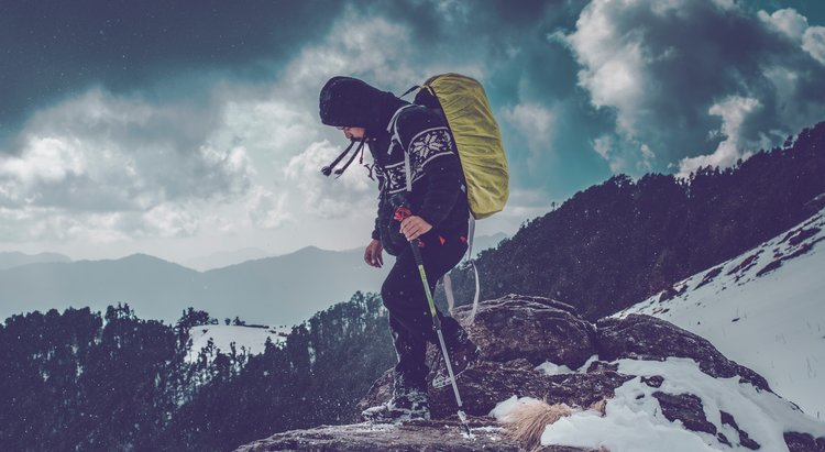 Man standing on top of a mountain covered in snow.
