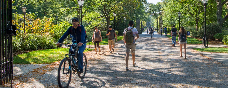 People walking and biking along path on campus