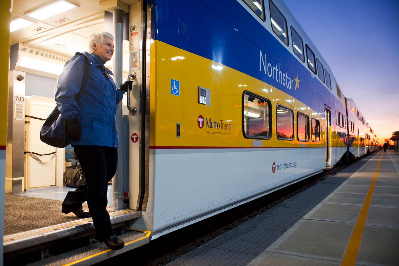 Content, happy gray-haired man stepping off the modern Northstar commuter train