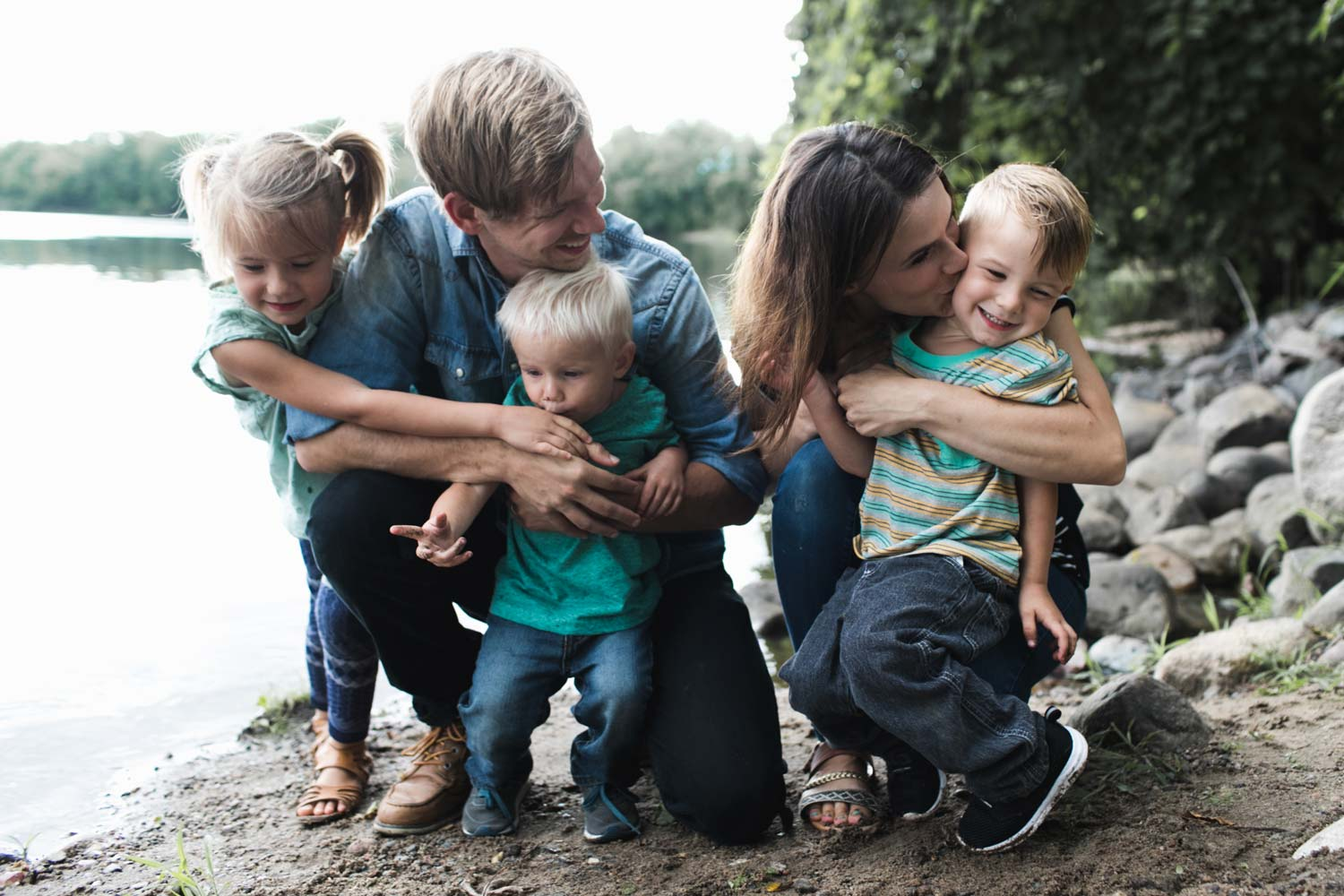 Mom and dad hugging kids on a rocky beach next to a river
