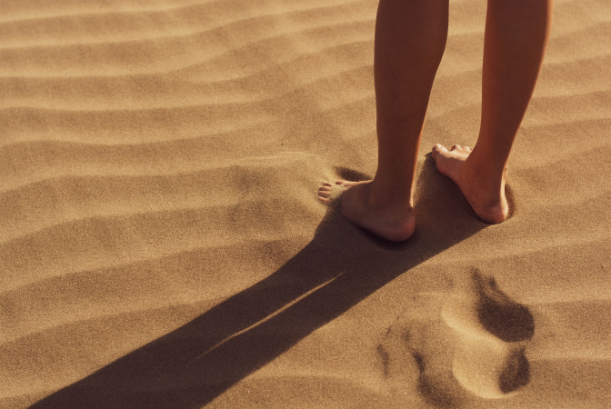 A human leaving footprints behind in the sand