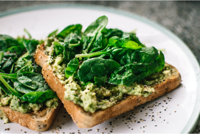 Avocado toast topped with spinach on plate
