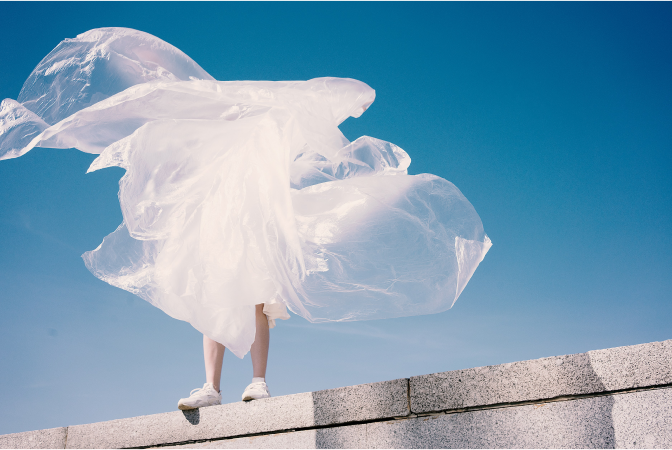 Person holding a large sheet of plastic tarp as the wind blows