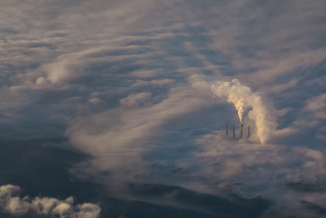 Greenhouse gases being released into Earth's atmosphere from a factory