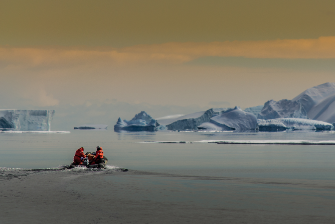 Climate scientists on a boat heading to study icebergs in the arctic