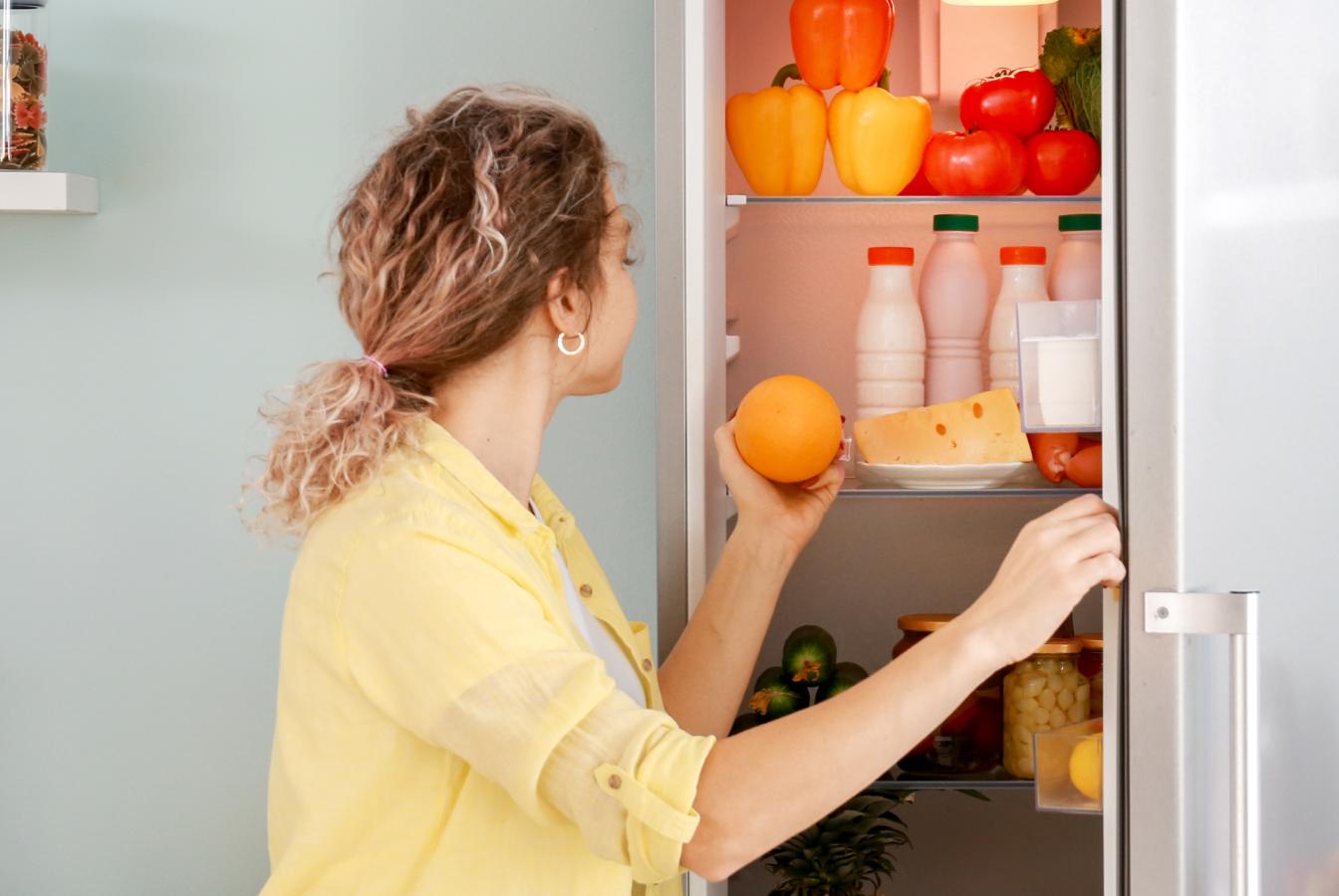 Woman opening fridge to retrive an orange