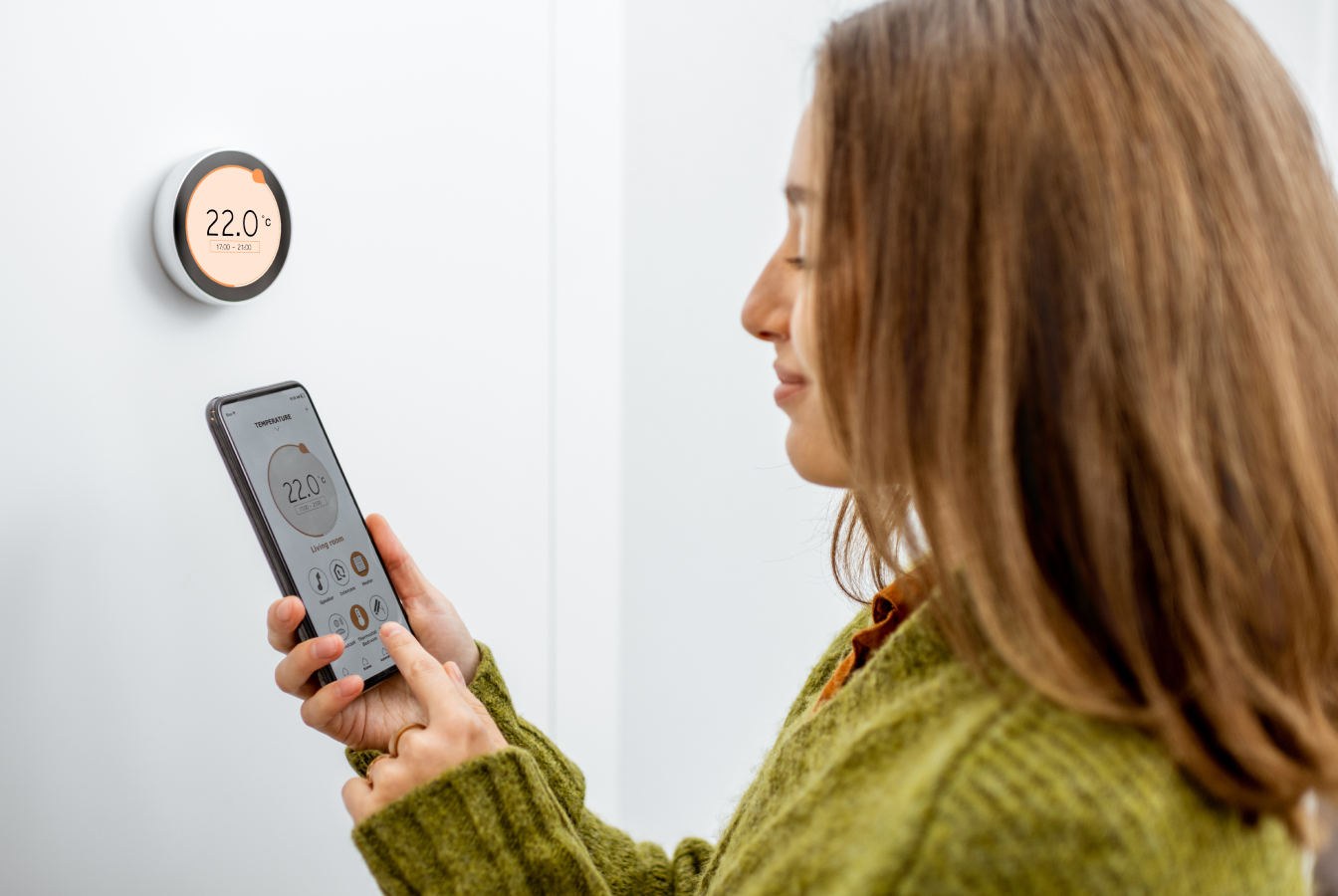 Woman using smart phone to adjust the heat on her thermostat