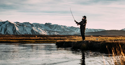man-casting-a-fishing-rod-in-chilly-weather-on-the-bank-of-a-calm-river-in-a-valley-with-snowy-mountains-in-the-distance-on-a-slightly-cloudy-day-during-sunrise