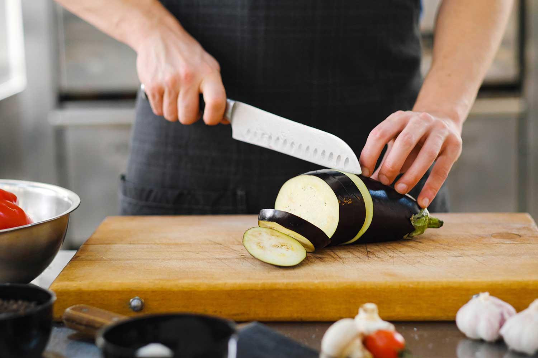 A person cutting eggplant on a cutting board