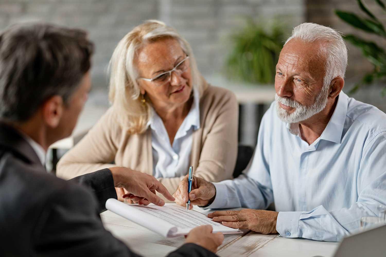 An elderly couple meeting with their advisor