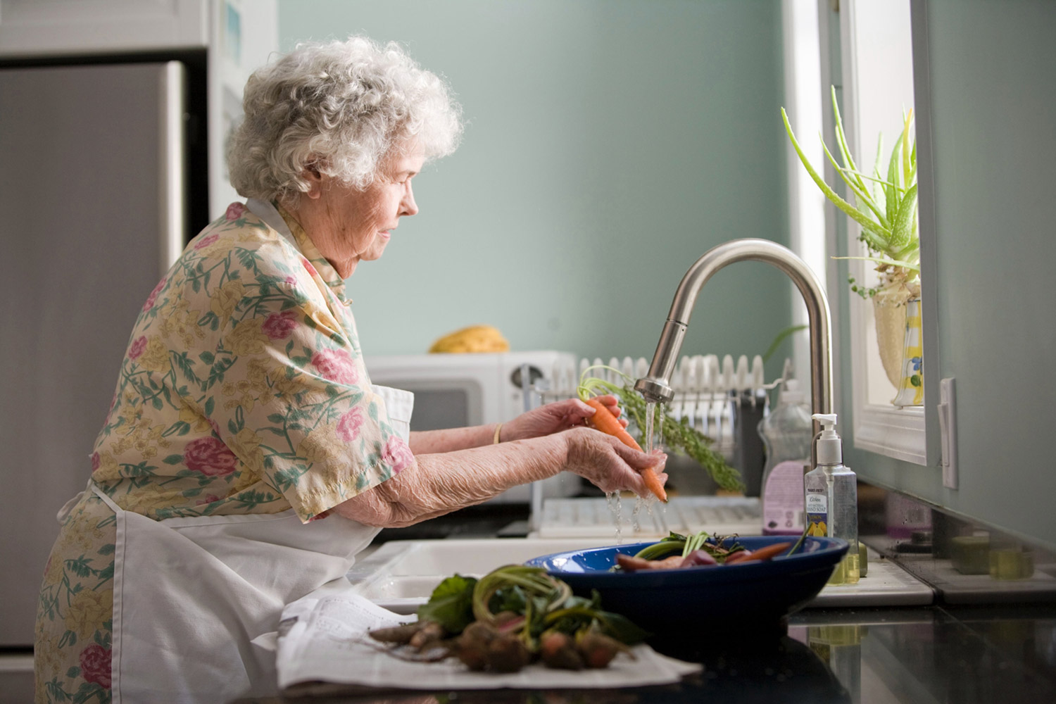 Older person washing food in a sink