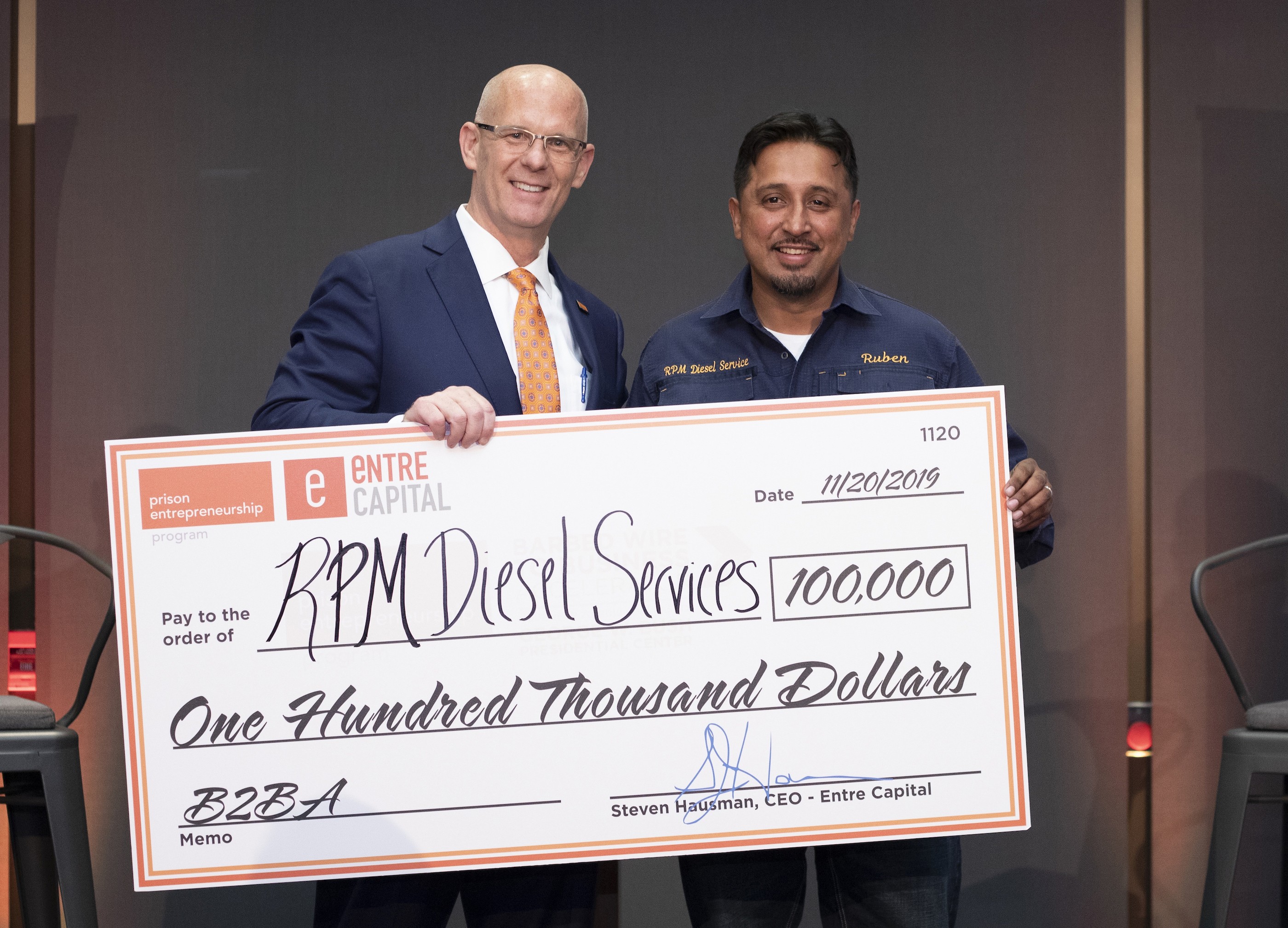 Two men posing with a large presentation check.