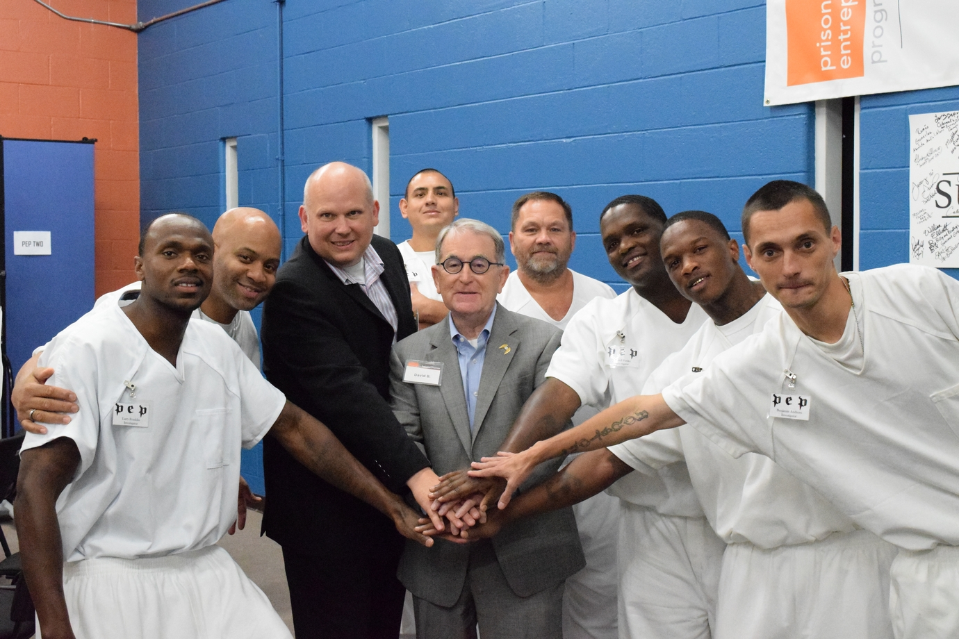 Several men, including some in prison uniforms, standing in a half circle with each man extending a hand to form a 'hand-stack'.