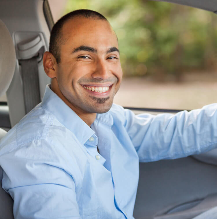 A man sitting in the driver seat of a vehicle, looks at the camera with a big smile.