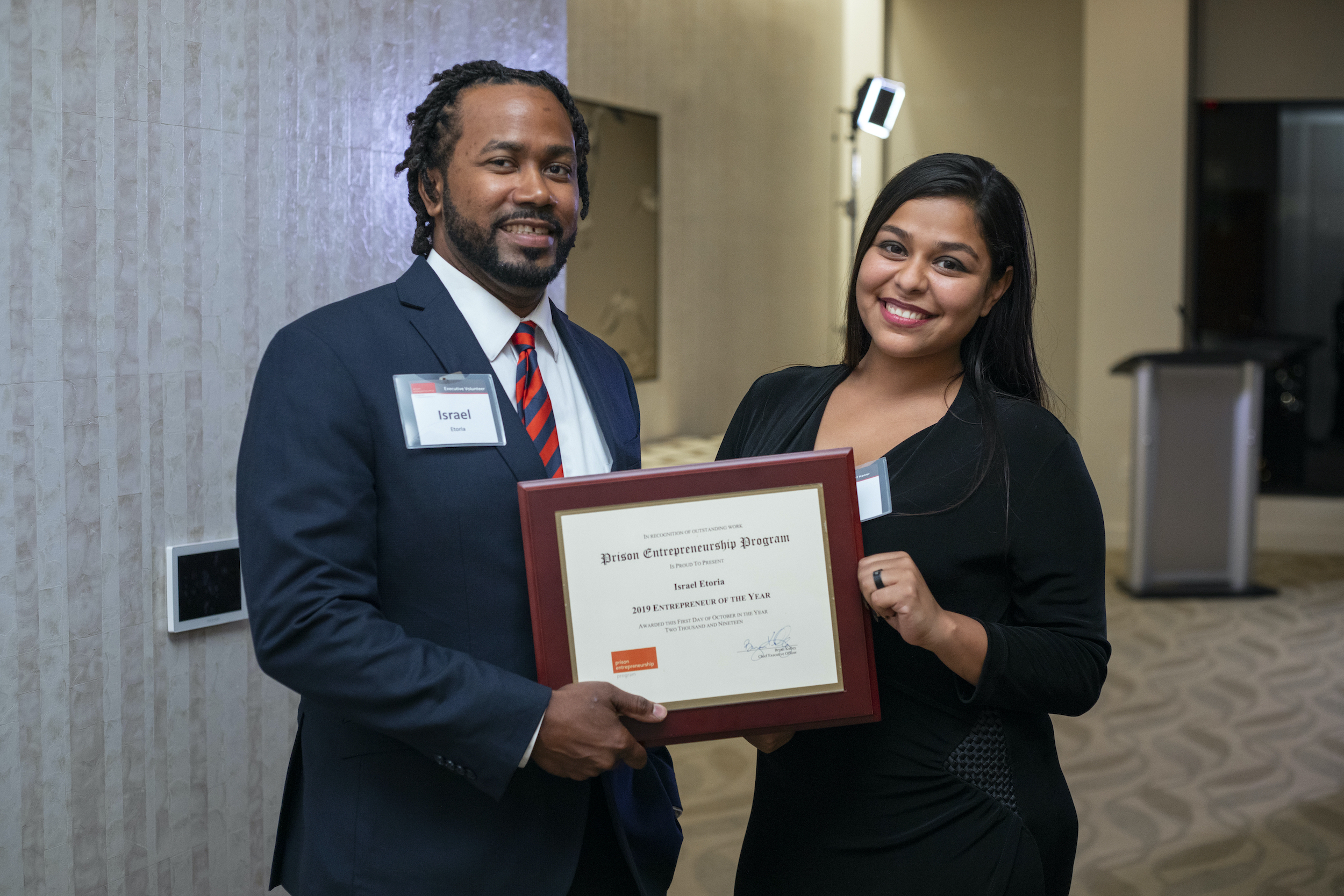 A man and a woman pose while holding a framed Prison Entrepreneurship Program Certificate.