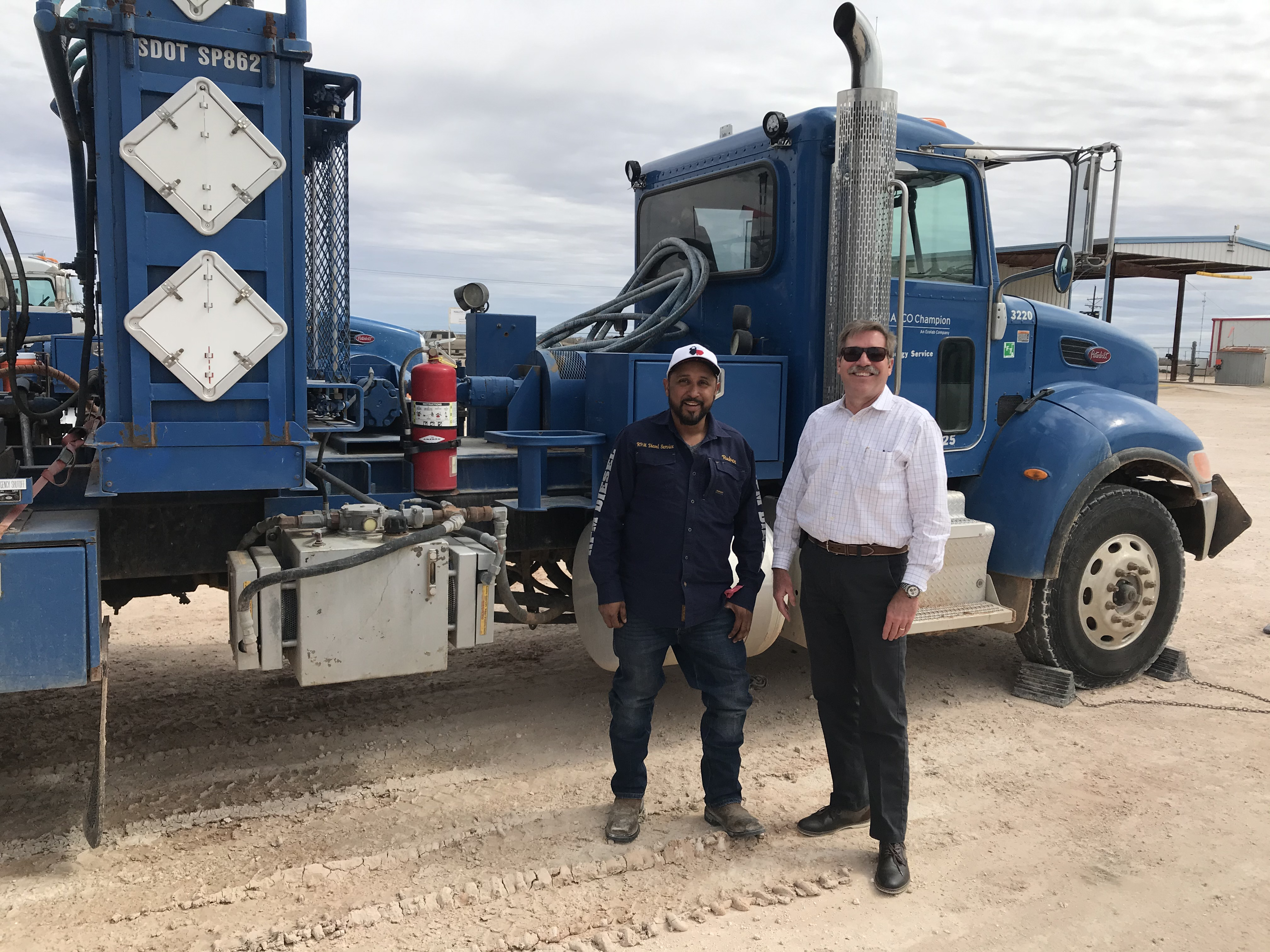 Two men standing in front of a blue semi truck.