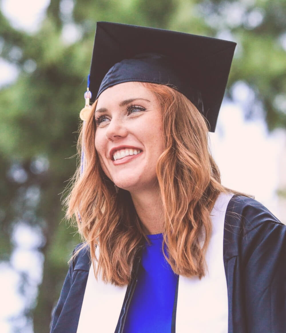 A woman in a cap and gown smiling