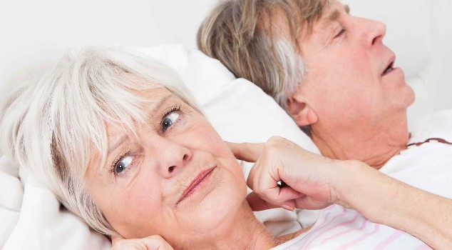 Woman frustrated with husbands snoring, covering her ears
