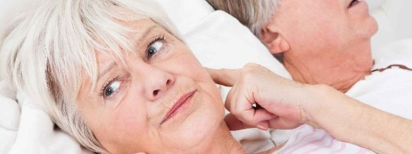 spouse tired of her husband snoring holding fingers in her ears