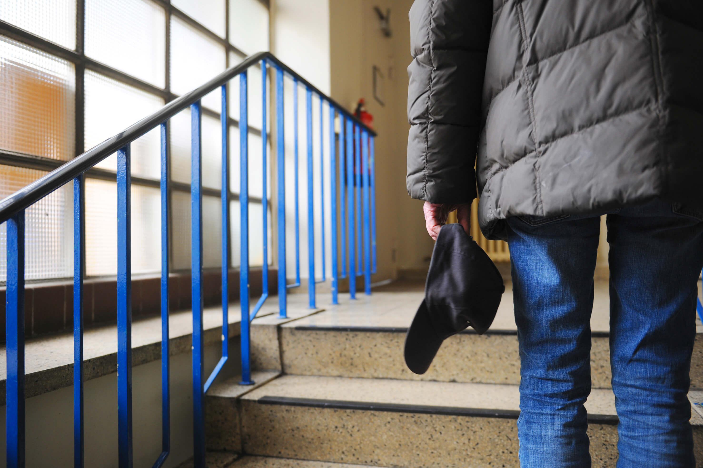 Obdachloser Mann auf der Treppe in der Einrichtung des Berliner Wohnforums