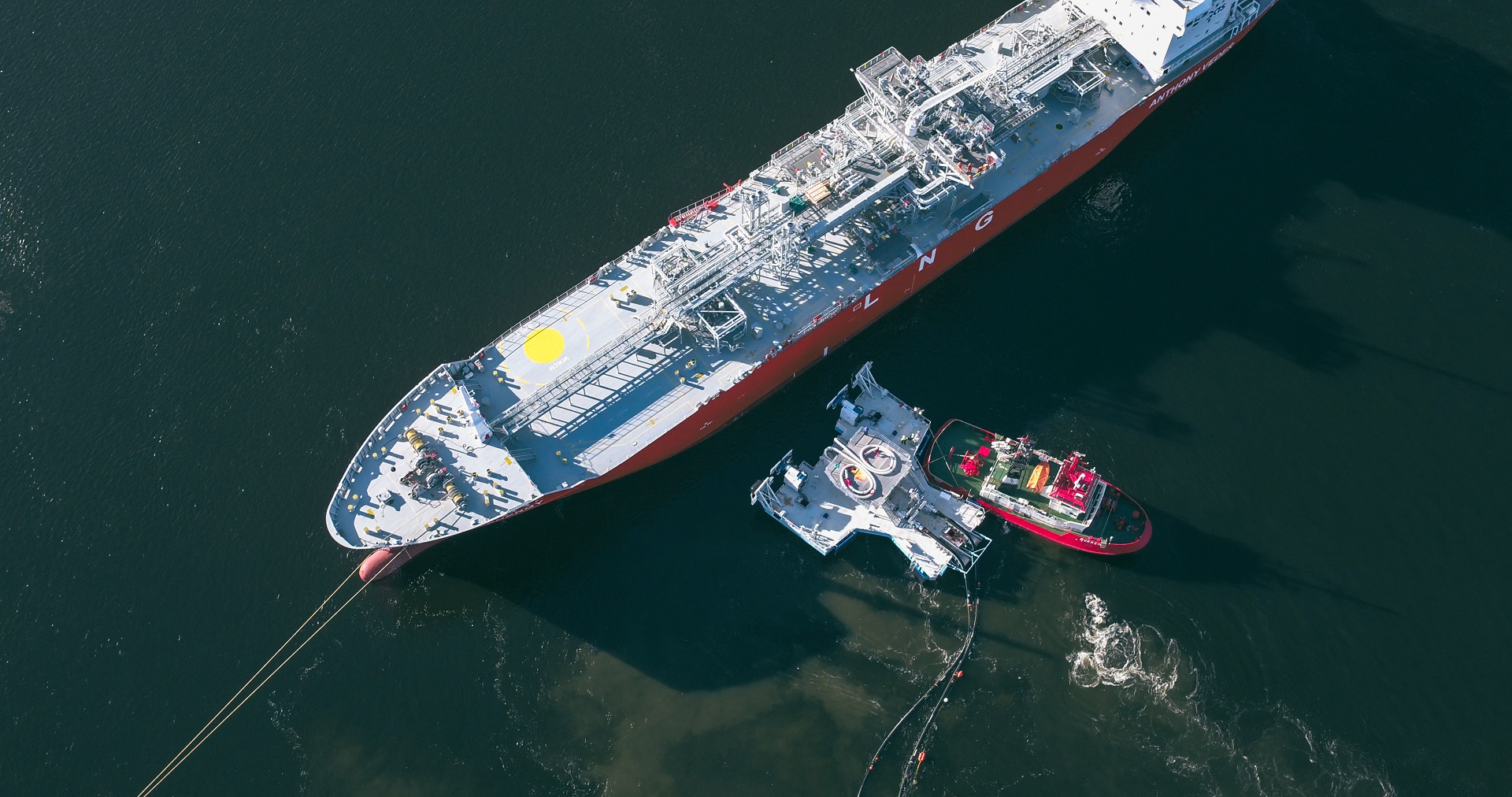 Floating jettyless transfer system connecting to an LNG carrier