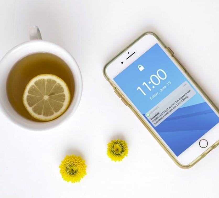 Soberlink app next to cup of tea
