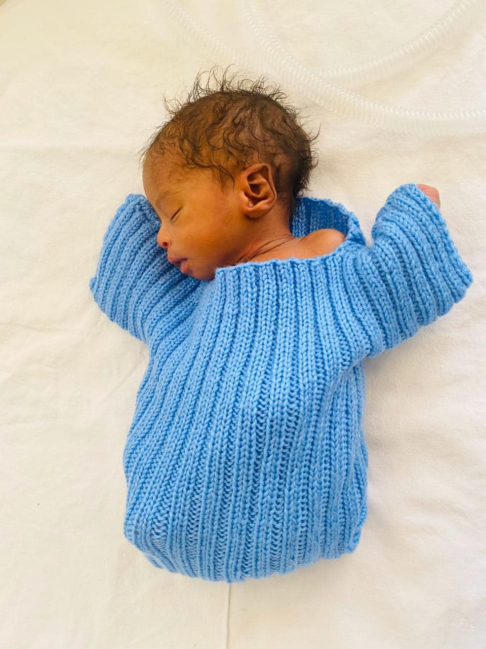 A premature baby, well covered in a baby wool knitted sweather