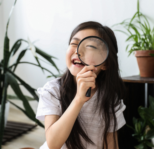 young girl looking through magnifying glass