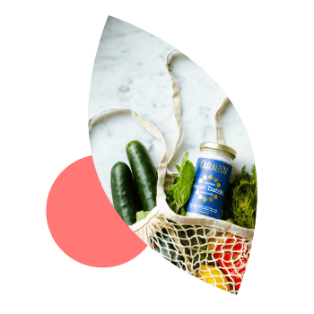 Reusable grocery bag filled with vegetables on top of a leaf illustration