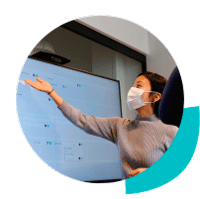 Professional woman in a protective mask giving a presentation in front of a monitor