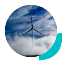Wind turbine emerging out of fog with blue sky and clouds in the background