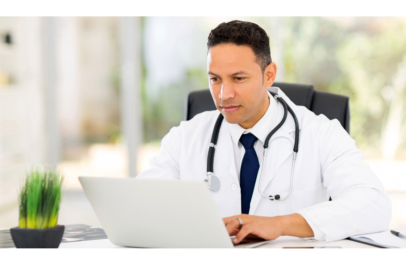 Male health care professional with stethoscope around neck working on laptop