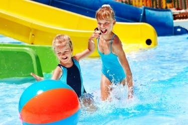 Kids playing in the water with a ball.