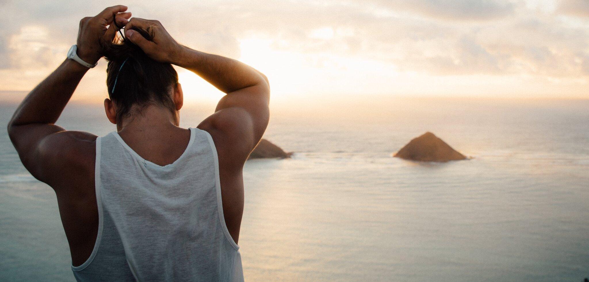 Mann in einem weißen Tanktop macht sich einen Zopf in die Haare | Joshua Munoz - Unsplas