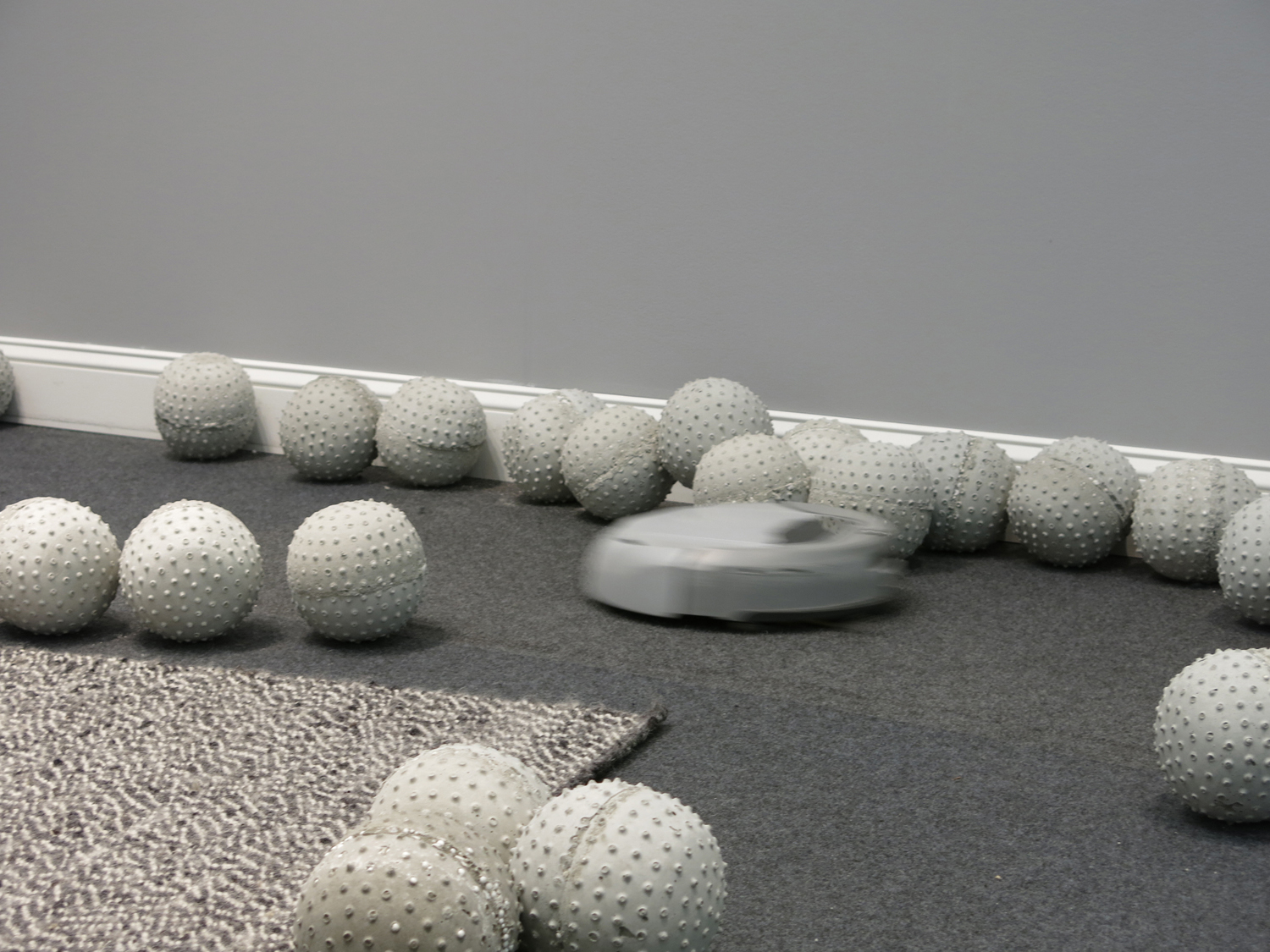 Nadim Abbas, Zone I, 2014. Lightweight concrete casts, robotic vacuum cleaner, rug, skirting board, house paint. Dimensions variable.