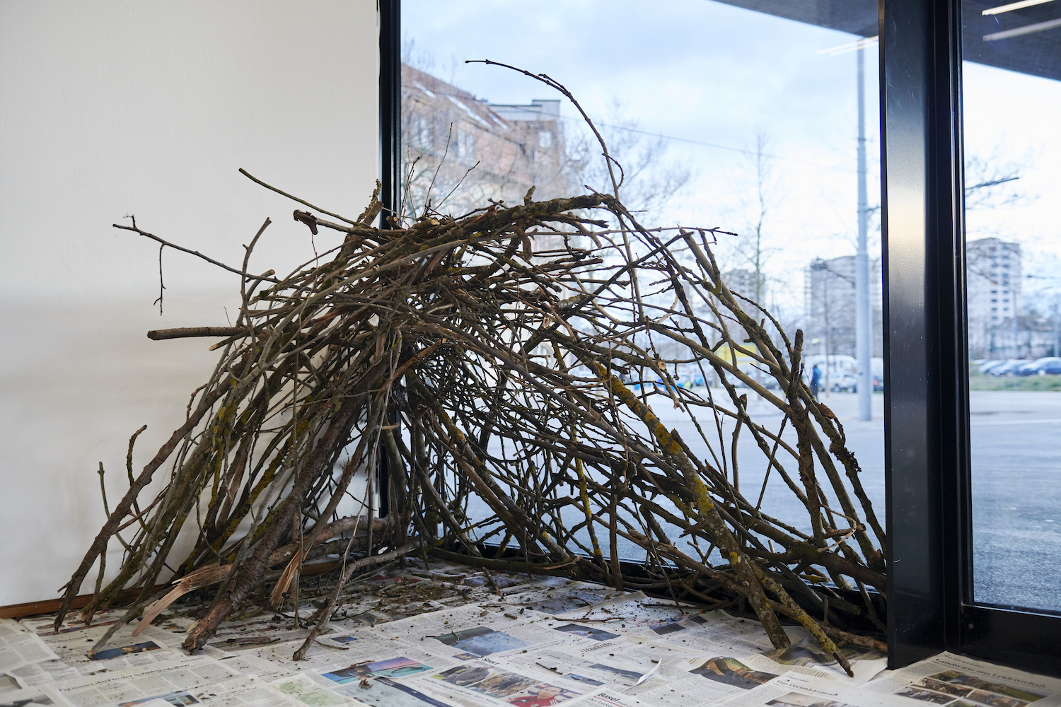 Suzanna Zak, Obedient Improvised Shelter (detail), 2020. Space blankets, found sticks, local newspapers. Dimensions variable. VITRINE, Basel. Photographer: Nici Jost.