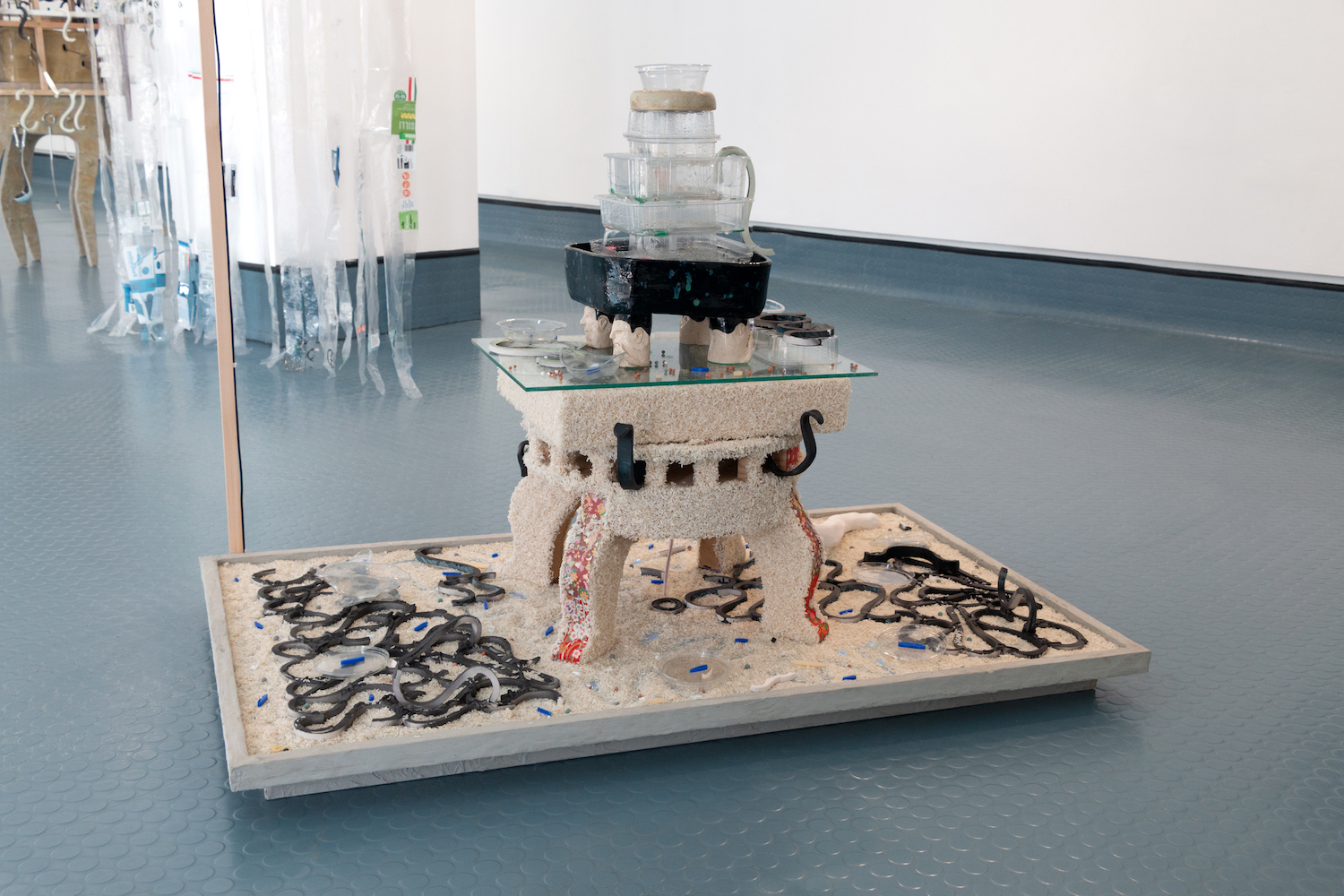 Kara Chin, Snack Fountain, 2019. Glazed ceramic, plastic containers, glass, paper, perspex, timber, tile grout, rice. 110 x 80 x 70 cm.