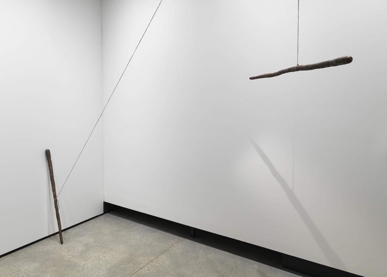 Sam Porritt, Carrot Shaped Stick, 2013. Cast Bronze, Lead, String (bronze casts). 100 x 5 x 5 cm.