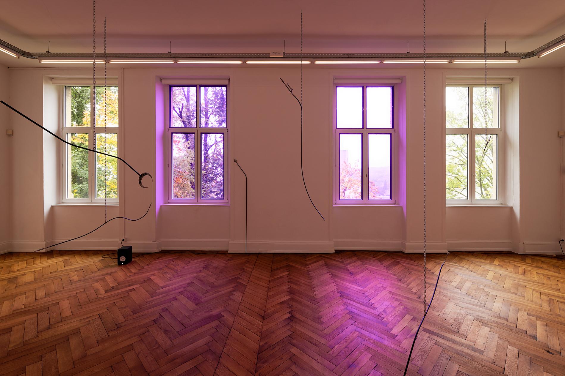 Tarek Lakhrissi, Unfinished Sentence, 2019. 10 metal spears, chains, colour filter, loud speakers. CRAC Alsace, Altkirch, FR. Photographer: Aurélien Mole.