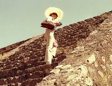 Lady with hat and purse walking up the side of an aztec pyramid.